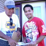 Volunteer, Herberto Figueroa, showing Kenosha resident the location of his polling place along with information needed to register.